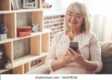 Beautiful mature woman in eyeglasses is using a smartphone and smiling while sitting on couch at home