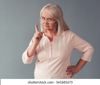Beautiful mature woman in eyeglasses is warning and looking at camera, on gray background