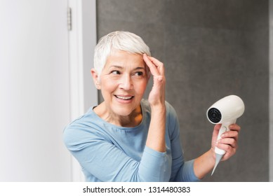 Beautiful mature woman full of energy with gorgeous smile and glowing skin drying her short gray hair with blowdryer at home