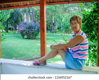 Beautiful mature woman with glasses enjoying life sits on stone fence in garden