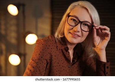 Beautiful mature woman in glasses at home
