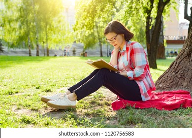 Beautiful mature woman with glasses reading book sitting on the grass near the tree in the park at sunset.