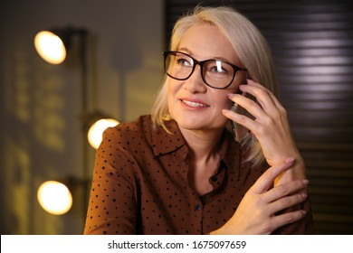 Beautiful mature woman in glasses talking on smartphone indoors