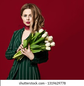 Beautiful mature woman hold bouquet of white tulip flowers for 8 march or Womans day on red background