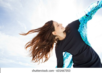 Beautiful mature woman holding raising silk fabric up against blue sky, floating in the breeze with sunshine, smiling outdoors. Dreamy positive joyful female enjoying healthy lifestyle, sun exterior.