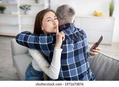 Beautiful mature woman hugging her husband, showing HUSH gesture, having secret affair, texting her lover on smartphone. Adultery, relationship issue, marriage cheating, hidden love concept