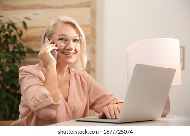 Beautiful mature woman with laptop talking on smartphone at home
