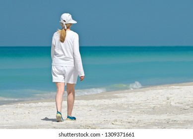 Beautiful Mature Woman Listening to Music while taking a leisure walk on the Beach.