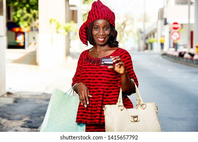 beautiful mature woman in loincloth standing outdoors showing credit card smiling with shopping bags.