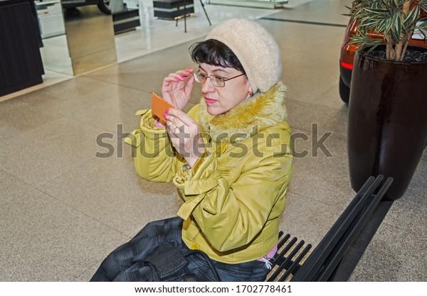 beautiful-mature-woman-looks-mirror-600w