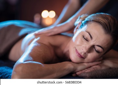A beautiful mature woman lying on a massage table in a beauty salon, while a professional therapist massages her back