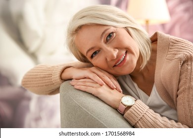 Beautiful mature woman on sofa at home