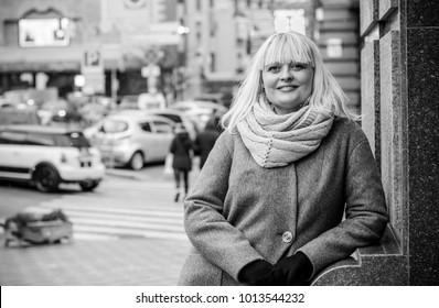 Beautiful mature woman on a walk in the city. Winter time. A nice middle aged plus size woman standing on the street. Citizen lifestyle