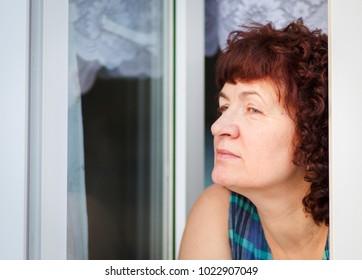 A beautiful mature woman peeking out the window, waiting.