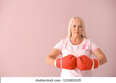Beautiful mature woman with pink ribbon and boxing gloves on color background. Breast cancer concept