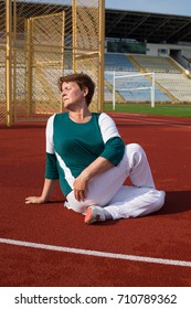 Beautiful mature woman practice yoga in spine twisting pose in red running stadium