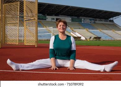 Beautiful mature woman practicing yoga stretching in red running stadium