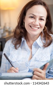 Beautiful mature woman relaxing at home writing or studying