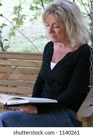 A beautiful mature woman relaxing and reading on her porch swing.