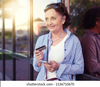 A beautiful mature woman retired 50 60 years old uses a bank card and a smartphone for shopping, online shopping, active retirees use modern technology