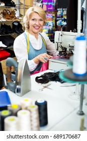 Beautiful mature woman sewing with professional machine at workshop