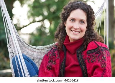 A beautiful mature woman sitting on a hammock