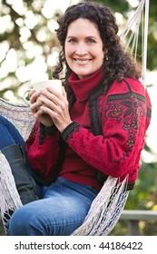 A beautiful mature woman sitting on a hammock drinking coffee