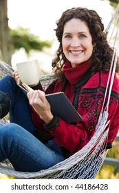 A beautiful mature woman sitting on a hammock reading a book