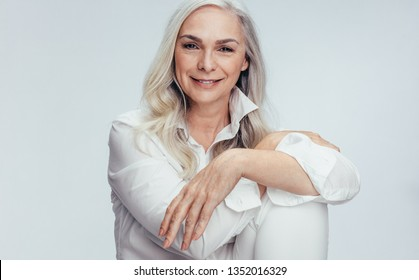 Beautiful mature woman sitting over white background. Senior woman sitting relaxed in studio.
