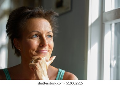 Beautiful mature woman smiling while thinking and looking out of window