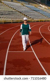 Beautiful mature woman in sports wear in red running stadium