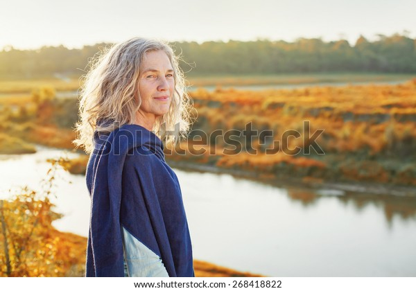 Beautiful mature woman standing in front of the river in autumn