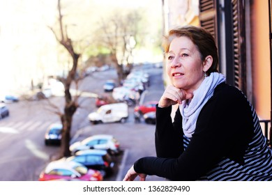 beautiful mature woman standing on the balcony looking to the street