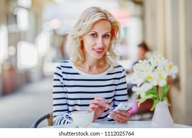 Beautiful mature woman surfing in the phone in a cafe on the street / copy space