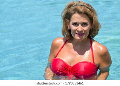 A Beautiful Mature Woman in the Swimmimng Pool Enjoying the Cool Water on a Hot Summer Day