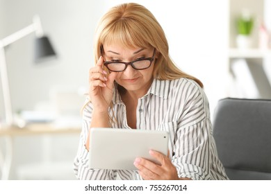 Beautiful mature woman with tablet computer at home