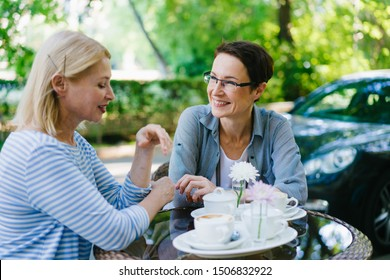 Beautiful mature woman is talking to female friend in street cafe smiling having fun enjoying warm summer day. Modern lifestyle, friendship and conversation concept.