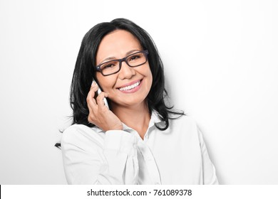 Beautiful mature woman talking on mobile phone on white background