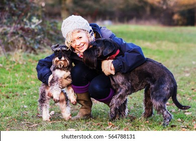 Beautiful mature woman walking dogs in the countryside