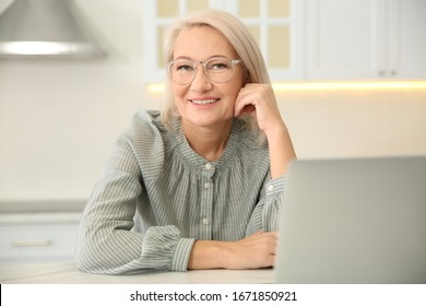 Beautiful mature woman working with laptop in kitchen