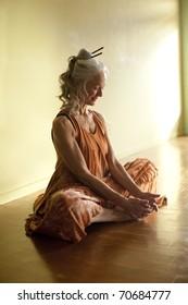 Beautiful mature woman in yoga pose baddhakonasana.