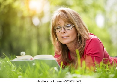 Beautiful mature woman.Happy woman reading a book during springtime in nature.