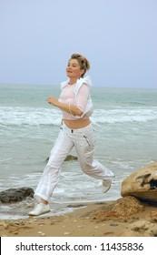 beautiful mature women running on a beach of sea