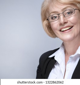 Beautiful Matured Woman happy cheerful caucasian in glasses toothy smile blond studio shot looking at camera. Grey background. Businesswoman in suit