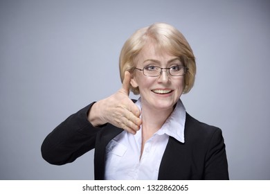 Beautiful Matured Woman happy cheerful caucasian in glasses toothy smile blond studio shot looking off camera. Lending her hand. copy space . Grey background. Businesswoman in suit