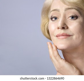 Beautiful Matured Woman Tauching her Face with hand. cheerful caucasian smiling blond. Studio shot. Looking off camera. Facecare. Grey background. 50 . Skin care concept