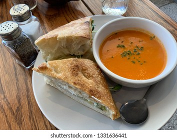 A beautiful meal with a gourmet grilled cheese sandwich made with homemade herbed focacia bread, cheddar, goat cheese, sprouts, apples, along with creamy tomato soup.