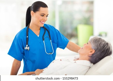 beautiful medical nurse talking to senior patient before checkup