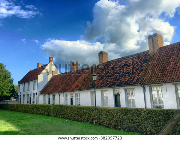 The beautiful medieval Beguinage of Hoogstraten, belgium, showing the row of white houses under a deep blue sky