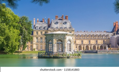 Beautiful Medieval landmark - royal hunting castle Fontainbleau timelapse hyperlapse with reflection in water of pond. Palace of Fontainebleau - one of largest royal chateaux in France, UNESCO World